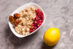 Cooked yummy warm oatmeal and heap of ripe fresh pomegranate seeds and three dried dates in white ceramic bowl. Near whole lemon on worn gray scratched concrete royalty free stock photos