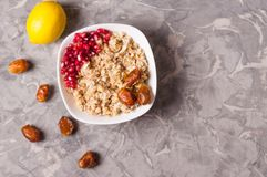 Cooked yummy warm oatmeal and heap of ripe fresh pomegranate seeds and three dried dates in white ceramic bowl. Near whole lemon and scattered dates on worn stock photo