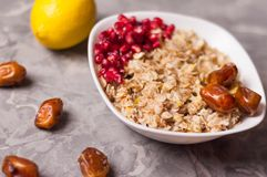 Cooked yummy warm oatmeal and heap of ripe fresh pomegranate seeds and three dried dates in white ceramic bowl. Near whole lemon and scattered dates on worn royalty free stock photography