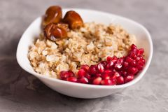 Cooked yummy warm oatmeal and heap of ripe fresh pomegranate seeds and three dried dates in white ceramic bowl. On worn gray scratched concrete royalty free stock photos