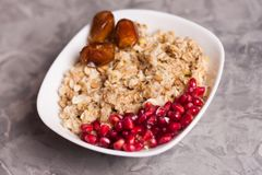 Cooked yummy warm oatmeal and heap of ripe fresh pomegranate seeds and three dried dates in white ceramic bowl. On worn gray scratched concrete stock photo