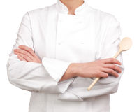 Cooker arms crossed holding a wooden spoon Stock Image