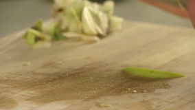 Cooker cutting fresh green apple on cookery board. Cooker cutting fresh green apple with a big knife on wooden cookery board in a cafe close up view stock footage