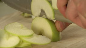 Cooker cutting fresh green apple on cookery board. Cooker cutting fresh green apple with a big knife on wooden cookery board in a cafe close up view stock video footage