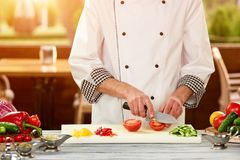 Cooker dicing tomato. Vegetable dicing on white desk. Tomato cutting Stock Photo