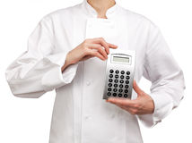 Cooker holding a calculator Royalty Free Stock Image