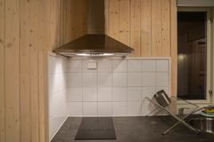 Cooker hood with electric stove in modern kitchen stock image