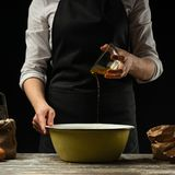 cookery De chef-kok bereidt het deeg voor deegwaren, pizza, brood, pannekoeken voor Voorbereiding en het werk met bloem en deeg H stock fotografie