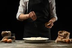 cookery De kok kookt deeg voor deegwaren, pizza, brood Bestrooit met zout Heerlijk voedsel, recepten, het koken, gastronomie, royalty-vrije stock foto's
