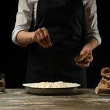 cookery De kok kookt deeg voor deegwaren, pizza, brood Bestrooit met zout Heerlijk voedsel, recepten, het koken, gastronomie, stock foto's