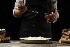 cookery De kok kookt deeg voor deegwaren, pizza, brood Giet water in de bloem Heerlijk voedsel, recepten, het koken, gastronomie, royalty-vrije stock fotografie