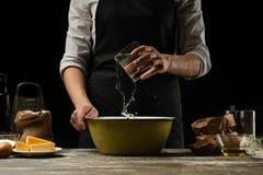 cookery De kok kookt deeg voor deegwaren, pizza, brood Giet water in de bloem Heerlijk voedsel, recepten, het koken, gastronomie, stock fotografie
