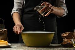 cookery De kok kookt deeg voor deegwaren, pizza, brood Giet water in de bloem Heerlijk voedsel, recepten, het koken, gastronomie, royalty-vrije stock foto