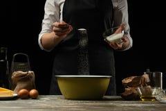 cookery O cozinheiro chefe prepara a massa para a massa, pizza, pão, panquecas Preparação e trabalho com farinha e massa Alimento fotografia de stock royalty free