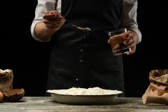cookery O cozinheiro cozinha a massa para a massa, pizza, pão Derrame a água na farinha Alimento delicioso, receitas, cozinhando, fotografia de stock royalty free