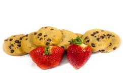 A stack of sweet fresh chocolate chip cookie`s and strawberry`s. A cookie is a baked or cooked food that is small, flat and sweet. It usually contains flour Stock Photo