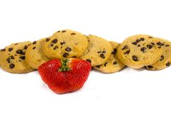Lot`s of sweet fresh chocolate cookie;s and a strawberry. A cookie is a baked or cooked food that is small, flat and sweet. It usually contains flour, sugar and royalty free stock photo