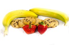 Yellow and green banana`s chocolate chip cookies strawberry`s. A cookie is a baked or cooked food that is small, flat and sweet. It usually contains flour, sugar Royalty Free Stock Image