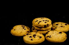 Fresh round sweet chocolate chip cookie`s in the dark. A cookie is a baked or cooked food that is small, flat and sweet. It usually contains flour, sugar and Royalty Free Stock Photos
