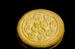 One round creme sandwich cookie. A cookie is a baked or cooked food that is small, flat and sweet. It usually contains flour, sugar and some type of oil or fat Royalty Free Stock Image