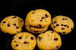 Fresh round sweet chocolate chip cookie`s in the dark. A cookie is a baked or cooked food that is small, flat and sweet. It usually contains flour, sugar and Stock Photography