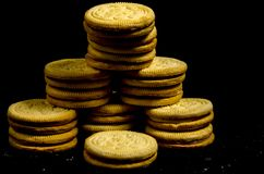 The big stack of round sweet cookie`s. A cookie is a baked or cooked food that is small, flat and sweet. It usually contains flour, sugar and some type of oil or Stock Images