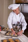 Cookie Baker. Uniformed female Baker forming cookie dough balls on baking tray Royalty Free Stock Photo