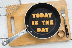 Cookie biscuits quote TODAY IS THE DAY in frying pan. Top view of alphabet text collage made of cookies biscuits. Quote TODAY IS THE DAY putting in frying pan Stock Photography