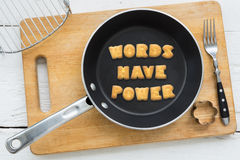Cookie biscuits quote WORDS HAVE POWER in frying pan. Top view of alphabet text collage made of cookies biscuits. Quote WORDS HAVE POWER putting in frying pan Royalty Free Stock Images