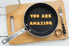 Cookie biscuits quote YOU ARE AMAZING in frying pan. Top view of alphabet text collage made of cookies biscuits. Quote YOU ARE AMAZING putting in frying pan Royalty Free Stock Image