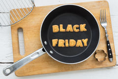 Cookie biscuits word BLACK FRIDAY in frying pan. Top view of alphabet text collage made of cookies biscuits. Word BLACK FRIDAY  in frying pan. Other utensils Stock Image