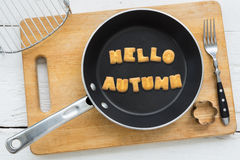 Cookie biscuits word HELLO AUTUMN in frying pan. Top view of alphabet text collage made of cookies biscuits. Word HELLO AUTUMN in frying pan. Other utensils Royalty Free Stock Images