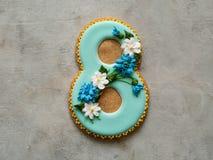 Cookie coberta com o esmalte azul feito numa forma do número oito com flores - centáureas e margaridas - no fundo cinzento ginger fotos de stock