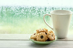 Cookie and coffee cup on rainy day window background Royalty Free Stock Images