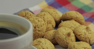 Cookie and cup of coffee. Kruidnoten, pepernoten, traditional sweets, strooigoed. Cookie and cup of coffee. Kruidnoten, pepernoten on colorful towel stock video footage
