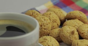 Cookie and cup of coffee. Kruidnoten, pepernoten, traditional sweets, strooigoed. Cookie and cup of coffee. Kruidnoten, pepernoten on colorful towel stock video