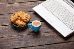 Cookie and cup with laptop Stock Image