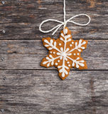 Cookie. Cute snowflake gingerbread cookie hanging by twine over a rustic wooden background royalty free stock image