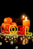 Cookie cutter building the word noel, tangerines and candle, bla Royalty Free Stock Images