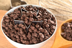 Cookie Cutter and Chocolate Chips. Star-shaped cookie cutter with chocolate chips in a bowl surrounded by baking utensils (Selective Focus, Focus on the front of Royalty Free Stock Images