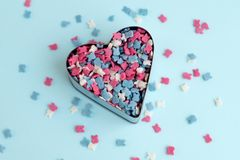 Cookie cutter with sprinkles. On blue background Royalty Free Stock Images