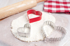 Cookie cutters in heart shape on dough Stock Photo