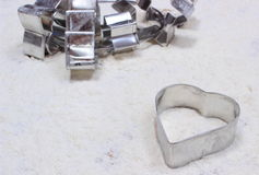 Cookie cutters lying on white flour Stock Images