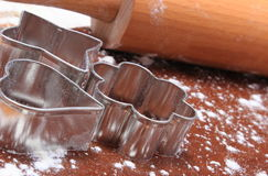 Cookie cutters and rolling pin on dough for cookies Royalty Free Stock Images