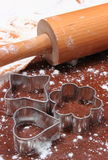 Cookie cutters and rolling pin on dough for cookies Royalty Free Stock Photography