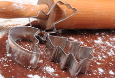 Cookie cutters and rolling pin on dough for gingerbread Royalty Free Stock Photography