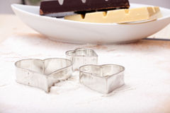 Cookie cutters and white and dark couverture Royalty Free Stock Photography
