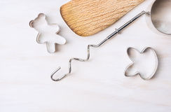 Cookie cutters and wooden spoon on white wooden Royalty Free Stock Images