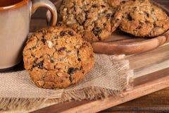 Cookie de farinha de aveia da noz-pecã da passa contra um copo de café Fotografia de Stock Royalty Free