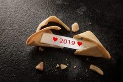 Cookie de fortuna chinesa quebrada com 2019 e corações vermelhos no pa imagens de stock